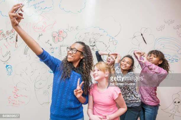 Girls taking selfie near whiteboard