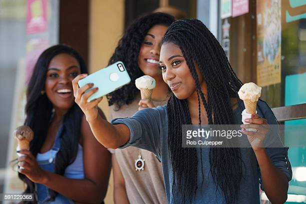Girls taking selfies and eating ice cream