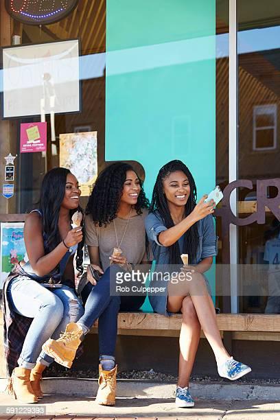 Girls taking selfies and eating ice cream