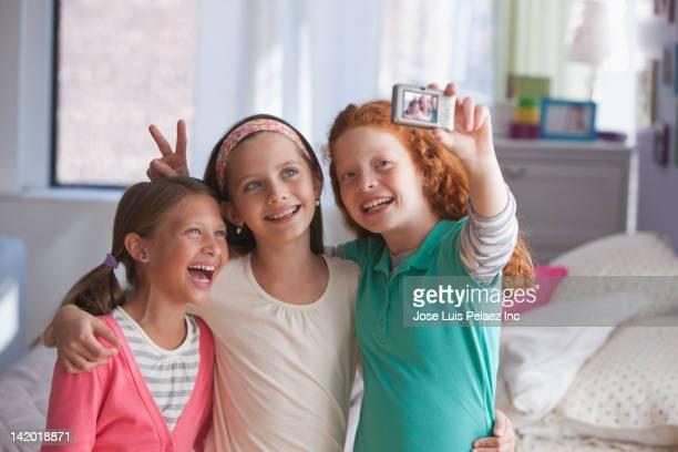 Girls taking self-portrait with digital camera
