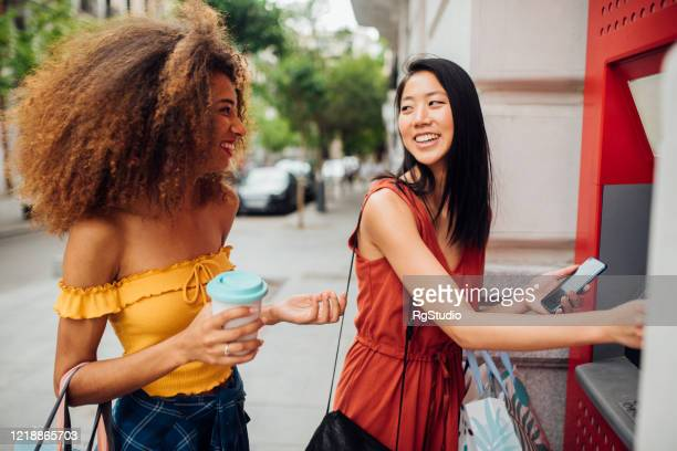 girls taking the money for shopping from atm machine - bank account stock pictures, royalty-free photos & images