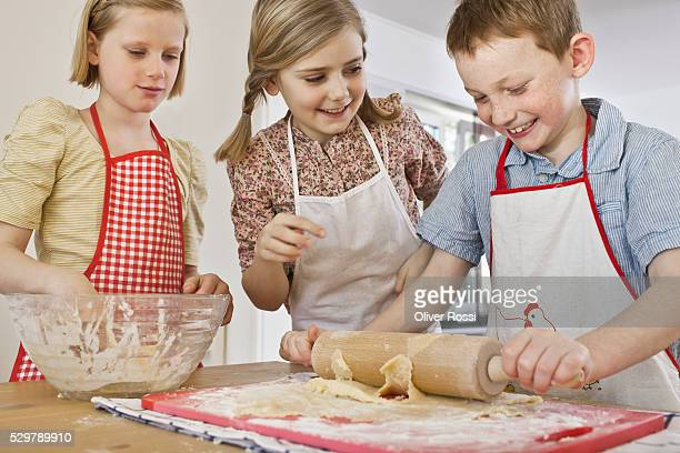 Girls (5-6) teaching boy (5-6) how to roll dough with roller pin