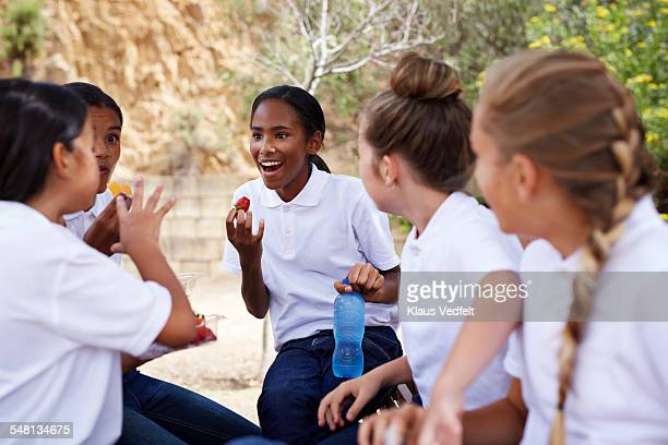 Girls telling stories and laughing in schoolyard