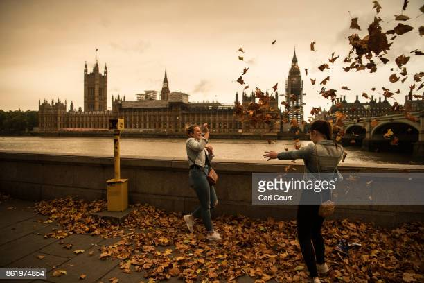 Girls throw leaves opposite the Houses of Parliament during a reddish sky caused by remnants of Hurricane Ophelia dragging in dust from the Sahara...