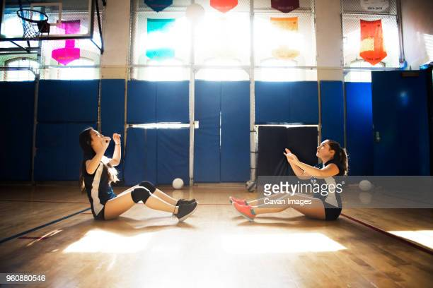 Girls throwing ball and practicing in volleyball court