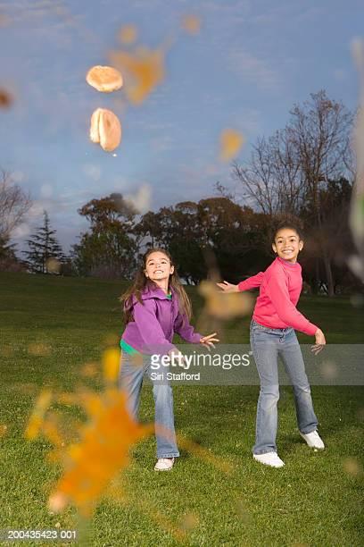 Girls (8-10) throwing food in park