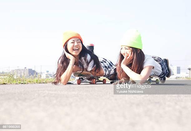girls to relax lying on skateboard - yusuke nishizawa stock pictures, royalty-free photos & images