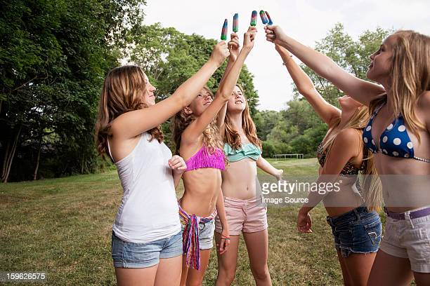 Girls toasting with ice lollies