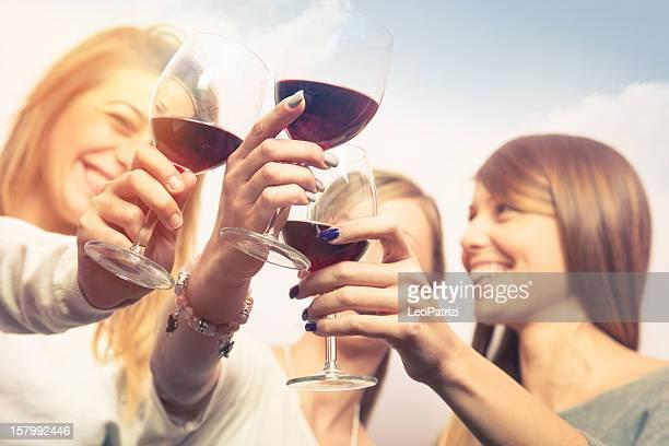 Mädchen Anstoßen mit Wein im Freien während der happy hour.