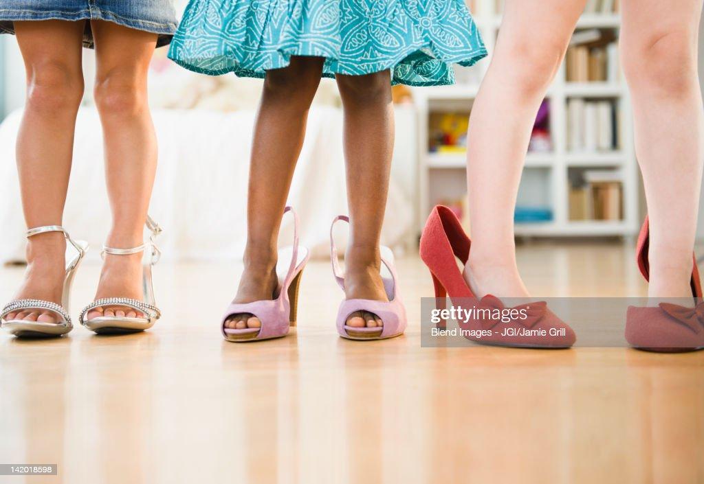 Girls trying on glamorous high-heeled shoes : Stock Photo