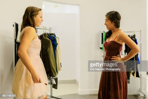 Girls trying on prom dresses in clothing store
