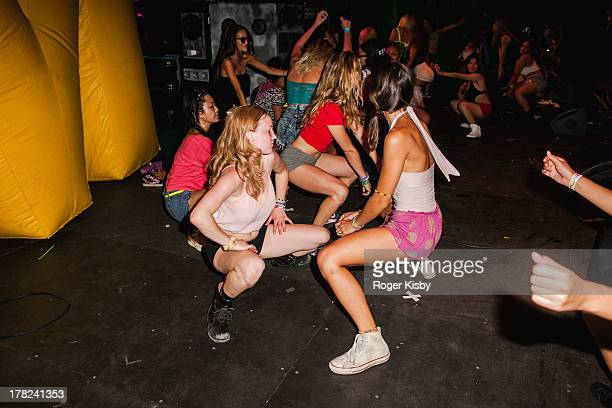 Girls twerk onstage during the performance of Major Lazer Mad Decent Block Party at Williamsburg Park on August 10 2013 in Brooklyn New York