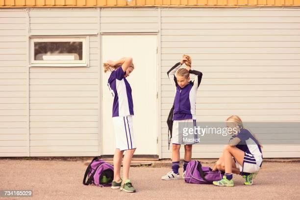 girls tying ponytail while friend crouching against wall - coda di cavallo foto e immagini stock