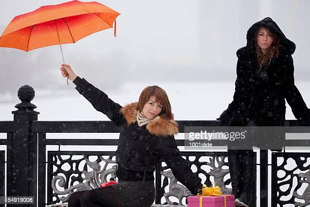 Mädchen: Unter Schneien mit orange Regenschirm und Geschenke