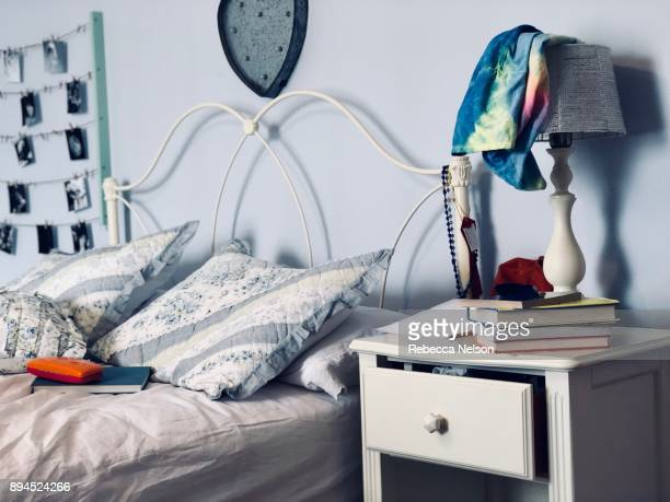 Girl's unmade bed with book and eye glass case