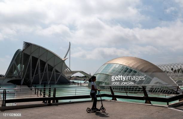 Girls uses a scooter at the City of Arts and Sciences cultural and architectural complex in Valencia on April 26 amid a national lockdown to prevent...