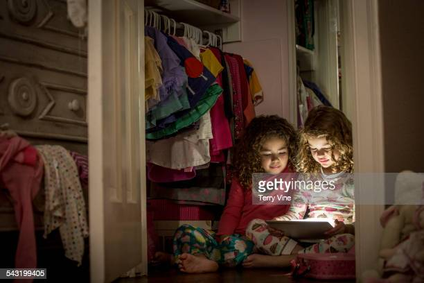 Girls using digital tablet in closet