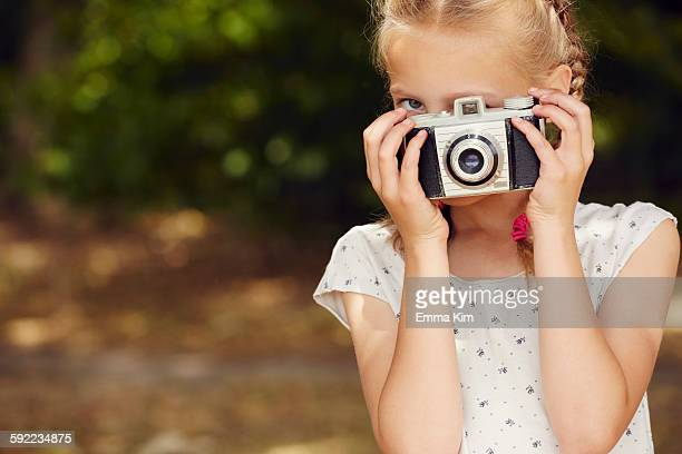 Girls using film camera, looking at camera face obscured
