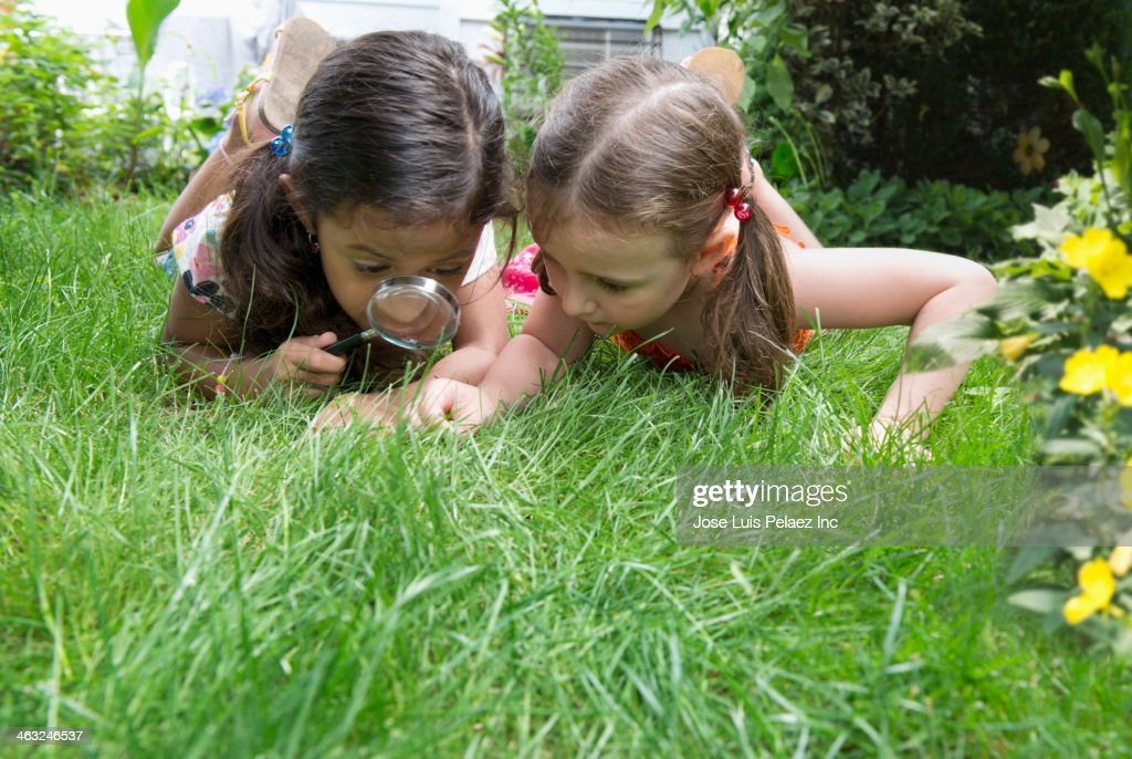 Girls using magnifying glass in grass : Stock Photo