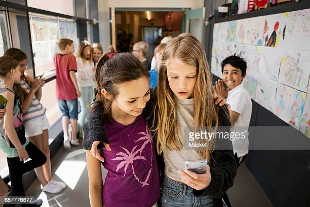 Girls using mobile phone with friends in corridor at school