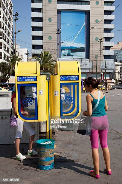 Girls using public telephones in Omonia Square Plateia Omonia is the center of Athens and is composed of the actual square together with the...