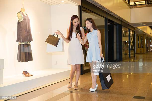 Girls using smart phone in a shopping mall