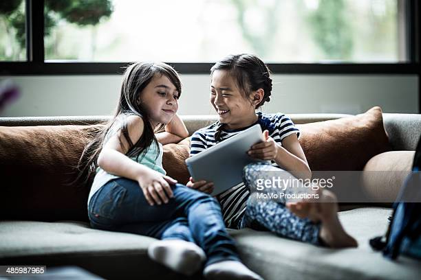 girls using tablet on couch