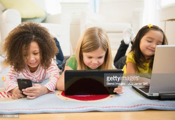 Girls using technology on carpet