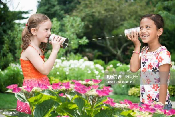 Girls using tin can telephone in backyard