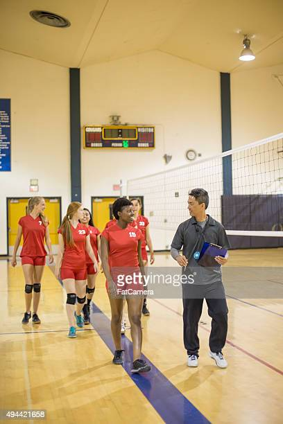 Girls volleyball players with coach after big win
