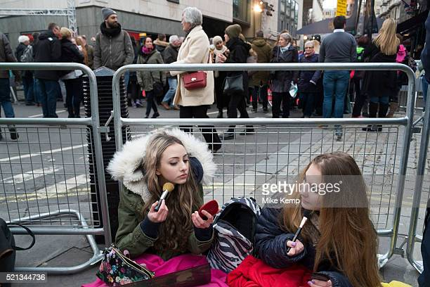Girls waiting to see their favourite movie stars outside the BAFTA Awards ceremony in London, England, United Kingdom. Izzy and Bella do their make...