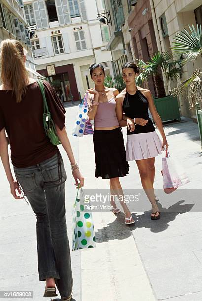 girls walk arm-in-arm down a shopping street staring at an approaching woman - girl wear jeans and flip flops stock photos and pictures
