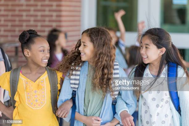 girls walk home from school arm in arm - pre adolescent child stock pictures, royalty-free photos & images
