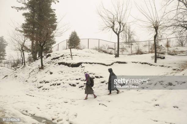 Girls walk on a snow covered road on January 30 2018 in Tangmarg some 40 kilometers north of Srinagar India The sevenweek dry spell ended in Kashmir...