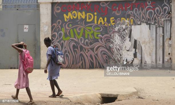 Girls walk past a graffiti reading 'Conakry World book capital' in Conakry on April 23 2017 Conakry is hosting the 'World book capital' event...