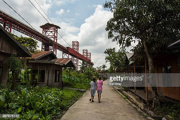 Girls walk past abandoned houses in a village which was largely abandoned several years ago after a coal mining company built a coal conveyor...