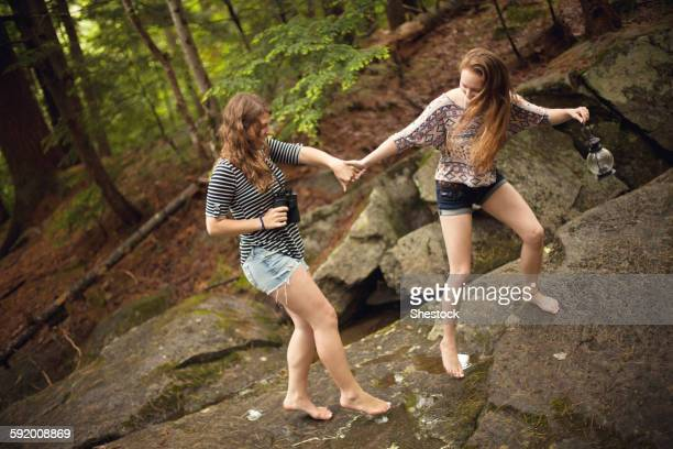 girls walking barefoot on boulder in forest - ragazzine scalze foto e immagini stock
