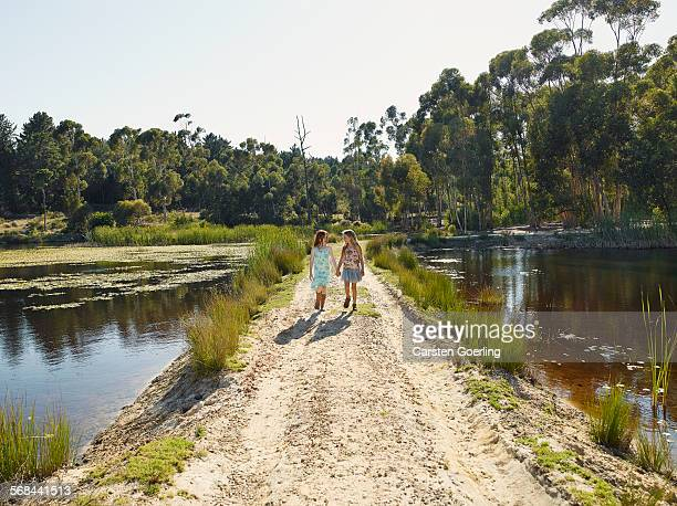 2 girls walking hand in hand at a lake