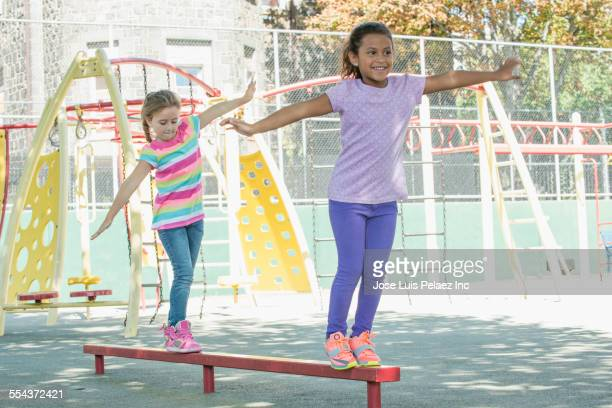 Girls walking on balance beam in park