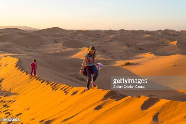 Girls walking on sand dunes in Sahara desert, Merzouga, Morocco