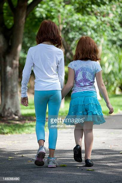 girls walking through park hand in hand - little girls up skirt stock photos and pictures
