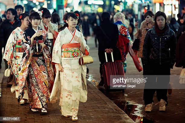 CONTENT] Girls walking through Shibuya shopping street wearing kimonos and fancy hair styles during the Coming of Age Day in Japan