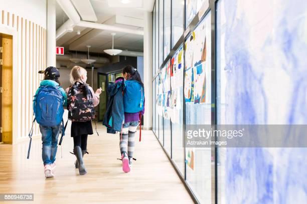 girls (8-9) walking together through school corridor - schoolgebouw stockfoto's en -beelden