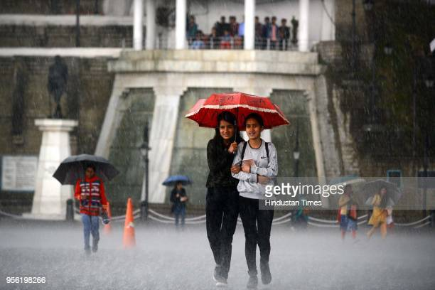Girls walking with umbrellas during heavy rain and hail storm at Ridgeon May 8 2018 in Shimla India Dust storms rain and thunder lashed out in parts...