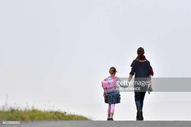 Girls walks to her primary school with her mother on the first day of the new school year in Vertou, western France, on September 4, 2017. / AFP...