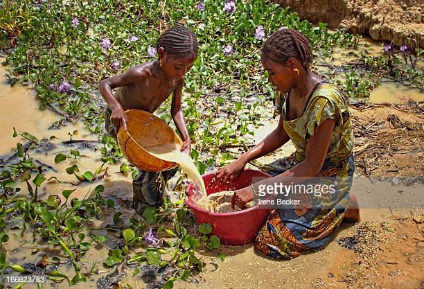Girls washing grains in pound near Argungu, Kebbi State, Nigeria. The girls are sisters. June 07, 2010.