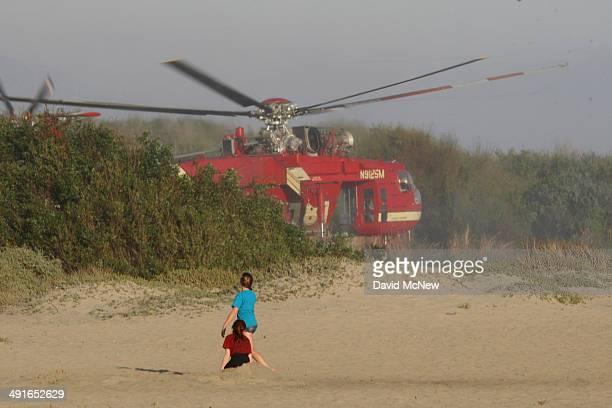 Girls watch an Erickson air crane firefighting helicopter suck water from a lagoon at Trestles surf beach to fight the Talega Fire on nearby Camp...