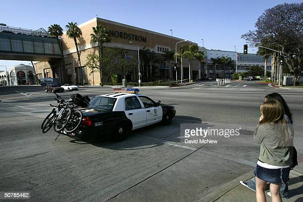 Girls watch Los Angeles police officers patrol near the Nordstrom store at the Westside Pavilion shopping mall as authorities step up security near...