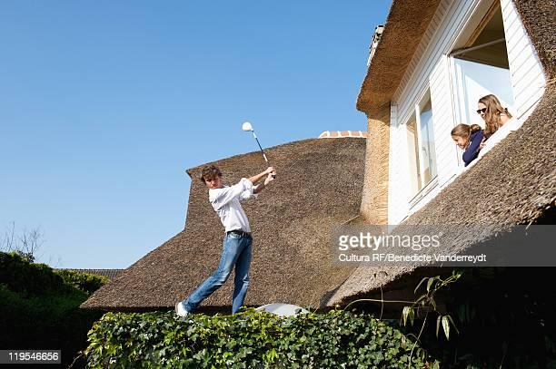 Girls watching boy play golf on roof