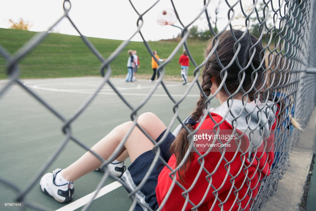 Girls watching boys playing basketball : Stock Photo